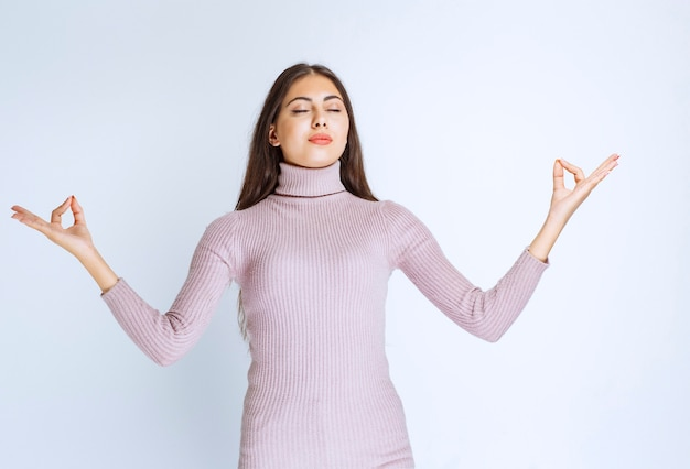 Frau im lila hemd, die meditation tut.