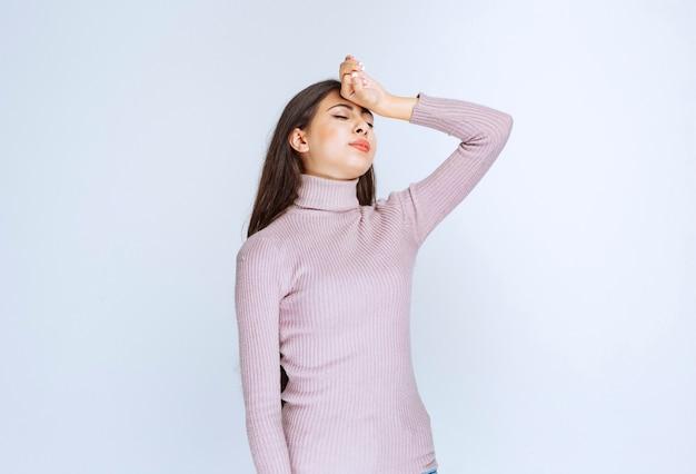 Frau im lila hemd ist schläfrig oder hat kopfschmerzen.