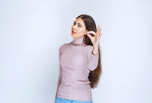 Frau im lila hemd mit freude handzeichen.