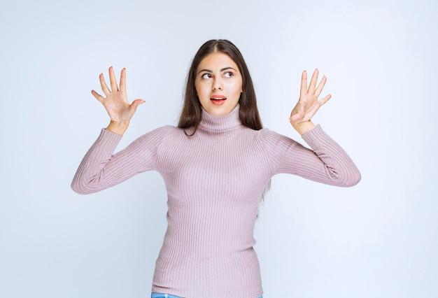 Frau im lila hemd sieht verängstigt oder verängstigt aus.