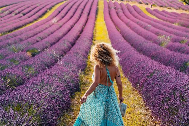 Frau im lockigen haar, das blaues kleid trägt und hut beim gehen im violetten lavendelfeld hält. rückansicht einer stilvollen frau im rückenfreien kleid inmitten eines wunderschönen lavendelfeldes