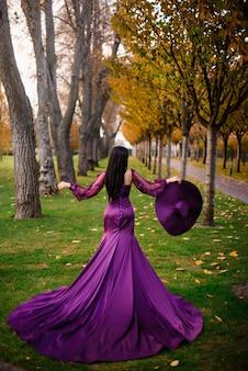 Frau im luxuriösen kleid steht im herbstpark