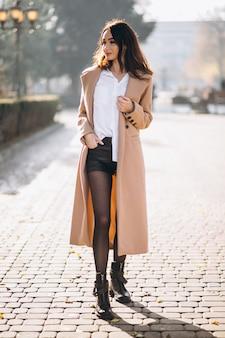 Frau im mantel außerhalb der th straße