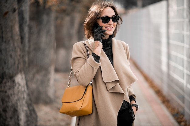 Frau im mantel mit telefon