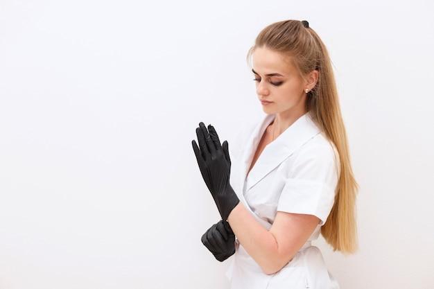 Frau im medizinischen kittel trägt schwarze medizinische handschuhe auf weißem hintergrund Premium Fotos