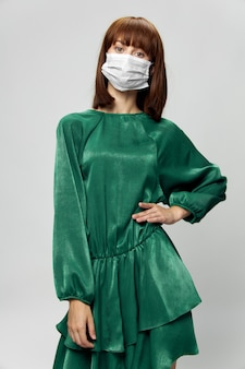 Frau im modekleid, das im medizinischen maskenvirus covid-19 aufwirft