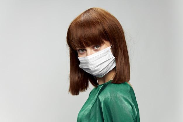 Frau im modekleid, das im medizinischen maskenvirus covid-19 aufwirft.