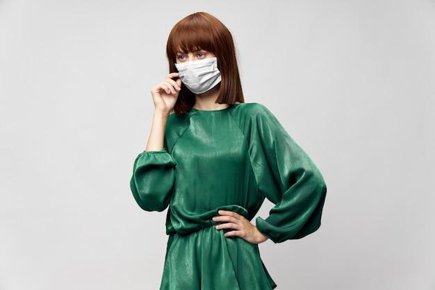 Frau im modischen kleid, das in der medizinischen maske aufwirft