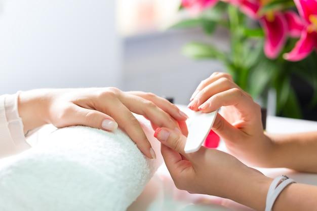 Frau im nagelsalon, der maniküre empfängt