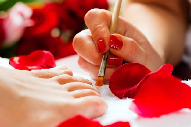 Frau im nagelstudio, das pediküre empfängt