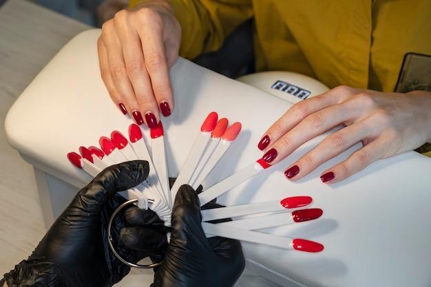 Frau im nagelstudio, die farbe des nagellacks wählt. gelpoliermittel. nagellack in verschiedenen farben.