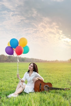 Frau im naturblumenfeld, das mit luftballons und gitarre aufwirft