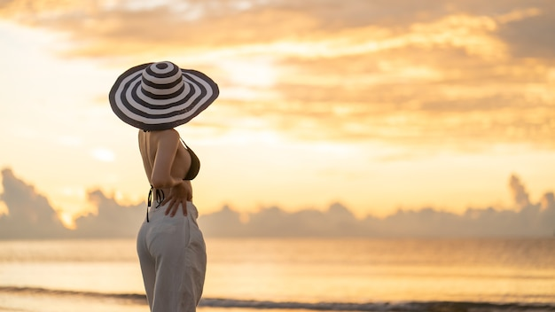Frau im oberen bikini und in der weißen langen hose, die hut am strand mit einem schönen sonnenaufgang trägt
