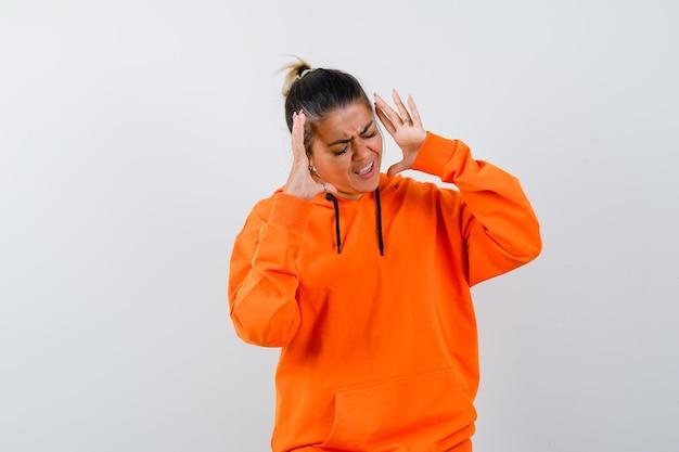 Frau im orangefarbenen hoodie, die aggressiv die hände hebt
