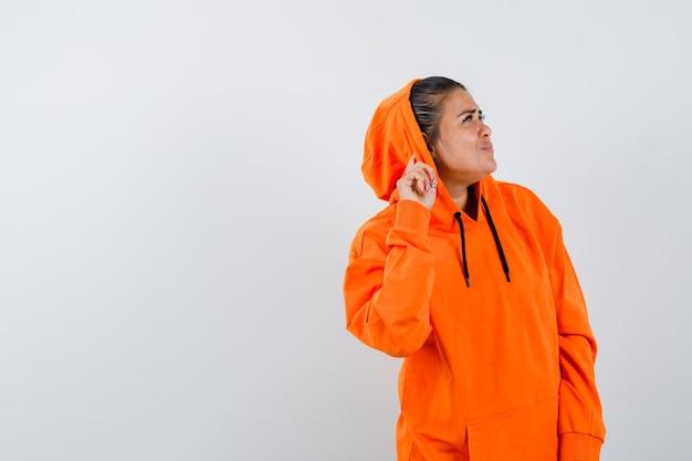 Frau im orangefarbenen hoodie, die ein privates gespräch belauscht und neugierig aussieht