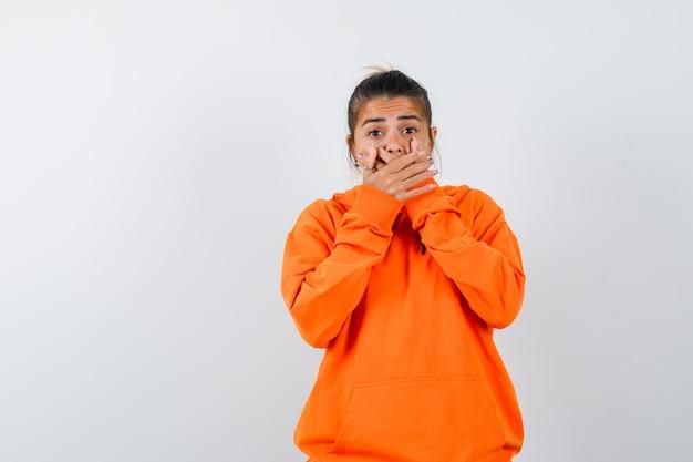 Frau im orangefarbenen hoodie hält die hände am mund und sieht schockiert aus