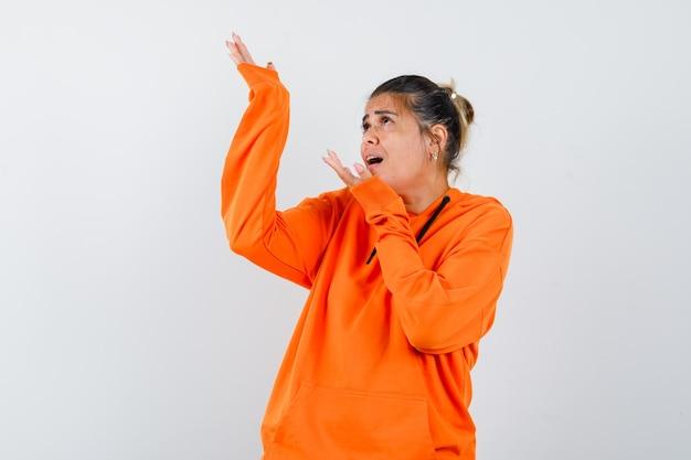 Frau im orangefarbenen hoodie macht willkommensgeste und sieht erstaunt aus