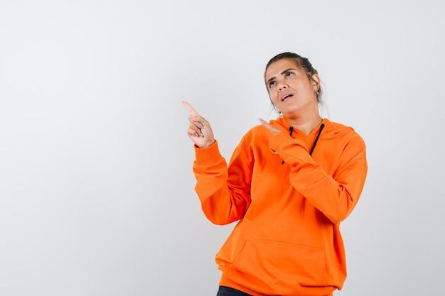 Frau im orangefarbenen hoodie zeigt auf die obere linke ecke und sieht verträumt aus looking