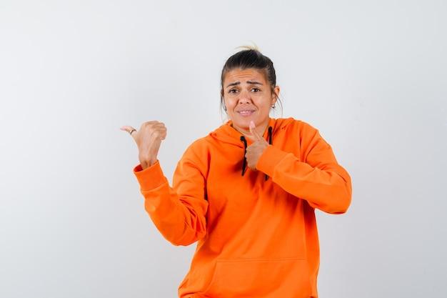 Frau im orangefarbenen hoodie zeigt daumen nach oben, zeigt zur seite und sieht verwirrt aus