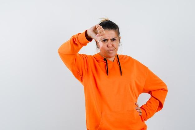 Frau im orangefarbenen hoodie zeigt daumen nach unten und sieht düster aus