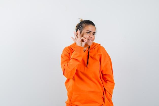 Frau im orangefarbenen hoodie zeigt eine ok geste und sieht fröhlich aus