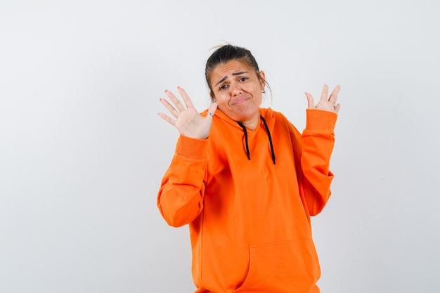 Frau im orangefarbenen hoodie zeigt handflächen in kapitulationsgeste und sieht verwirrt aus looking
