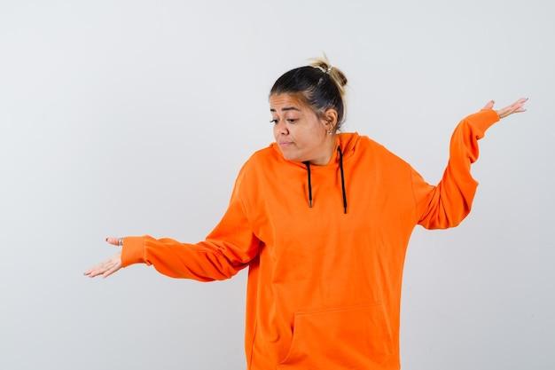 Frau im orangefarbenen hoodie zeigt hilflose geste und sieht verwirrt aus