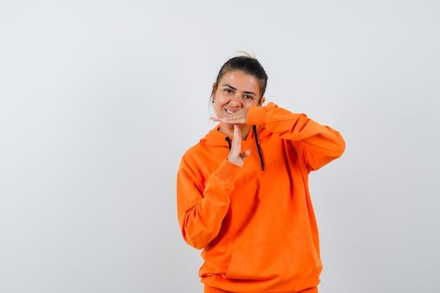 Frau im orangefarbenen hoodie zeigt zeitpausengeste und sieht fröhlich aus