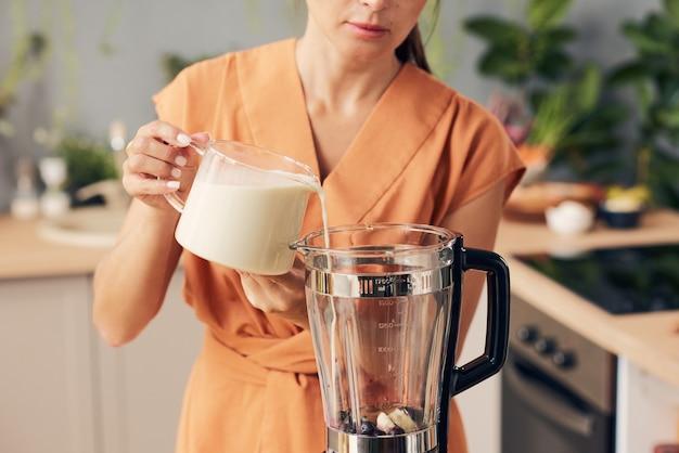 Frau im orangefarbenen kleid, die frische milch in elektrischen mixer gießt