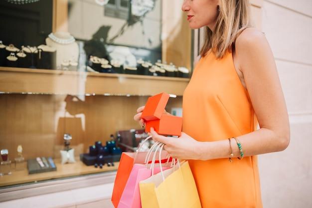 Frau im orangefarbenen kleid vor juweliergeschäft
