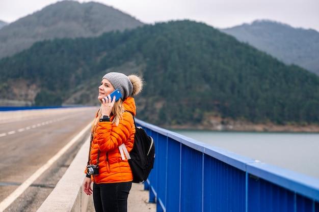 Frau im orangefarbenen mantel und im wollhut unter verwendung eines mobiltelefons auf einer straße in einer brücke