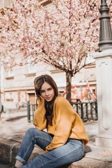 Frau im orangefarbenen pullover sitzt auf der straßenstraße. charmantes mädchen in jeans, die außerhalb nahe blühender sakura aufwerfen. dame schaut in die kamera