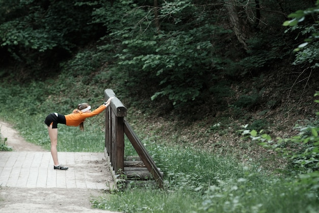 Frau im orangefarbenen sport-kapuzenpulli, der sich vor dem joggen aufwärmt