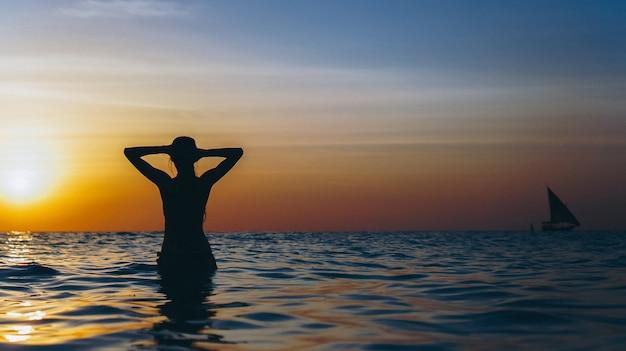 Frau im ozean in der sonnenuntergangzeit