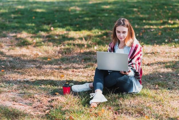 Frau im park, der an laptop arbeitet