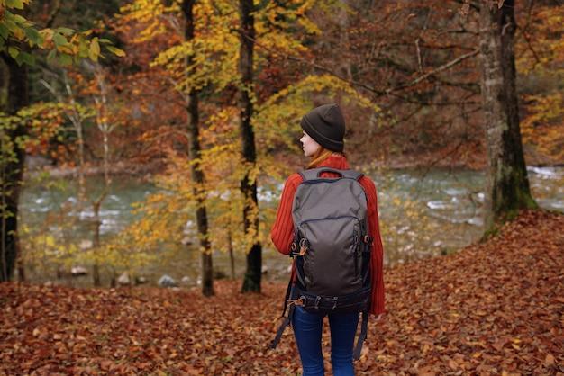 Frau im park im herbst nahe dem fluss und einem rucksack auf ihrer rückansicht