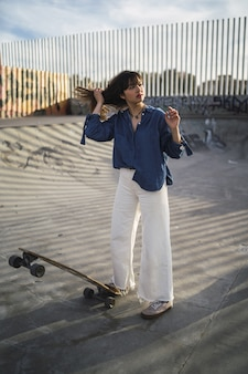Frau im park mit einem skateboard