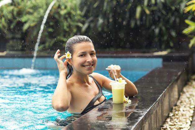 Frau im pool mit fruchtgetränk.