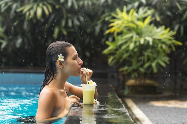 Frau im pool mit fruchtgetränk