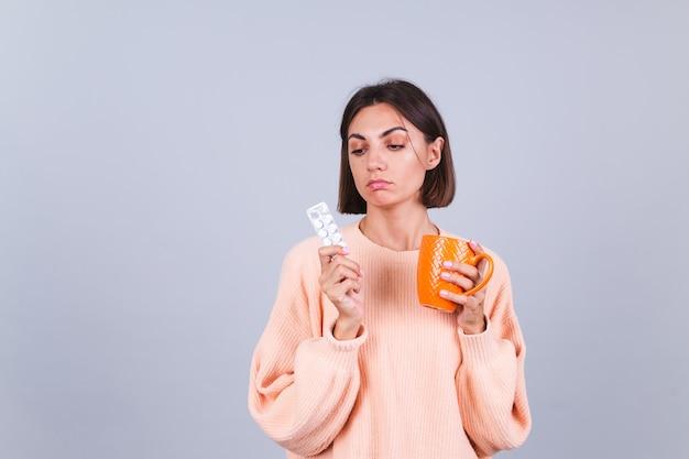 Frau im pullover an grauer wand hält becher und pillen mit unglücklichem traurigem gesichtsausdruck