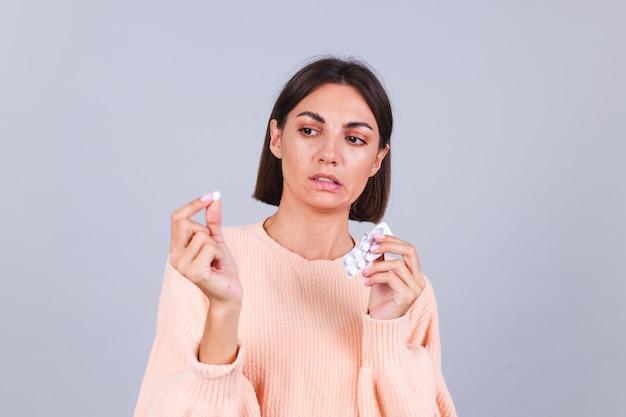 Frau im pullover an grauer wand hält pillen mit unglücklichen traurigen blicken auf pille mit ekel