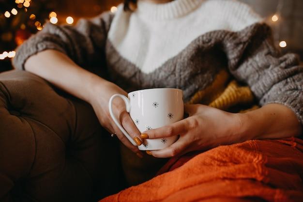 Frau im pullover, eine tasse kaffee oder tee zu hause haltend