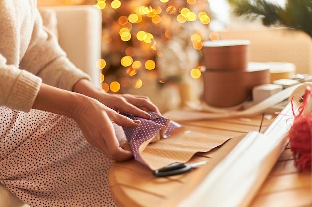 Frau im pullover sitzt und verpackt geschenke