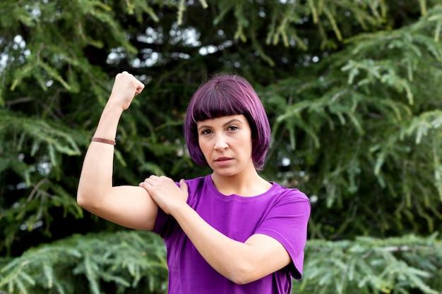 Frau im purpur, das ihr bizeps zeigt