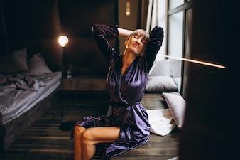 Frau im purpurroten Bademantel im Schlafzimmer