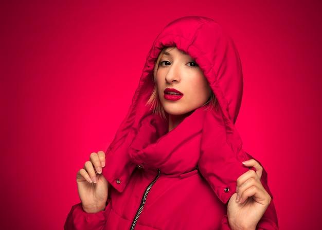 Frau im purpurroten hintergrund der roten wintermit kapuze jacke