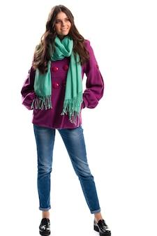 Frau im purpurroten mantellächeln. jeans und schwarze hochglanzschuhe. frühlingsoutfit mit buntem schal. fleece-kleidung von hoher qualität.