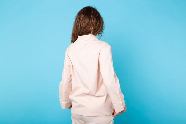 Frau im pyjama auf blauem hintergrund. entspannen sie sich bei guter laune, lifestyle und nachtwäsche. rückansicht.