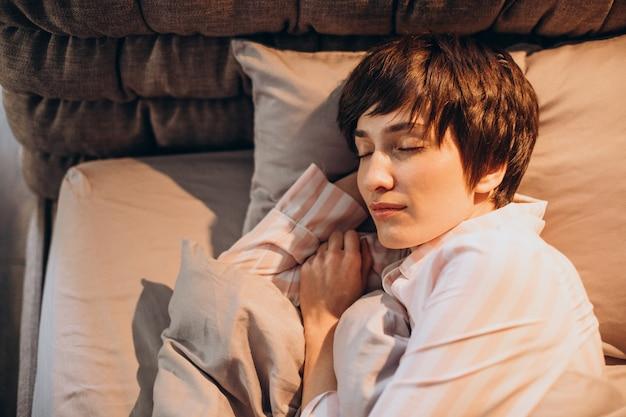 Frau im pyjama, die im bett aufwacht