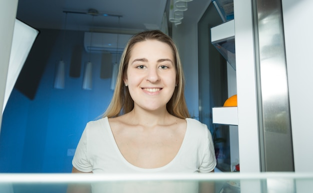 Frau im pyjama, die spät in der nacht zu hause in den kühlschrank schaut